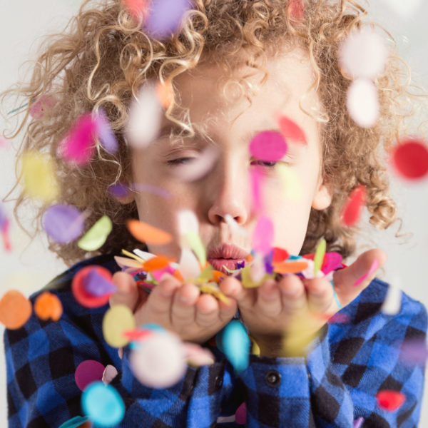 Sweet young boy with curly hair blowing colorful confetti